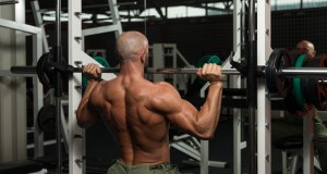 Mature Man Doing Shoulder Exercises In The Gym